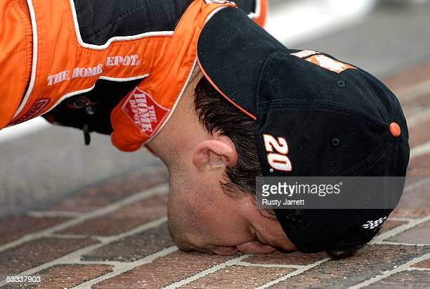 Tony Stewart driver of the Home Depot Chevrolet kisses the bricks after winning the NASCAR Nextel Cup Series Allstate 400 on August 7 2005 at the...