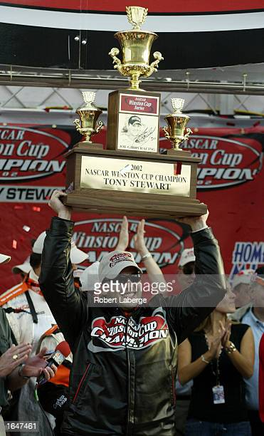 Tony Stewart driver of the Home Depot Pontiac Grand Prix lifts the NASCAR Winston Cup Championship trophy at the NASCAR Winston Cup Series Ford 400...