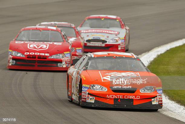 Tony Stewart driver of the Joe Gibbs Racing Chevrolet Monte Carlo leads a pack of cars during the NASCAR Pocono 500 at the Pocono Raceway on June 8...
