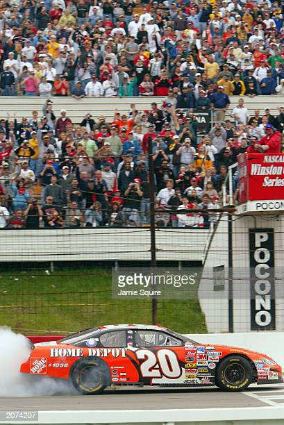 Tony Stewart driver of the Joe Gibbs Racing Chevrolet Monte Carlo performs a burnout in front of the cheering crowd while celebrating his victory in...