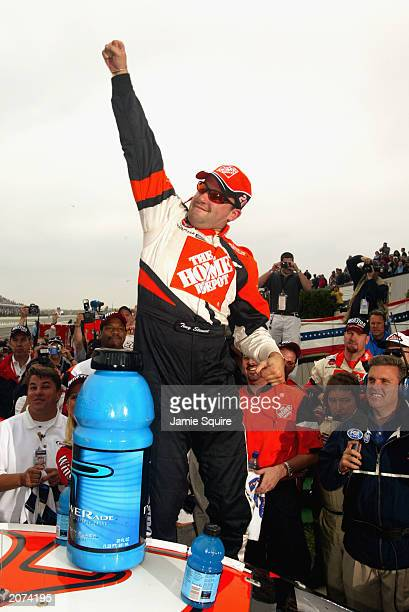 Tony Stewart driver of the Joe Gibbs Racing Chevrolet Monte Carlo celebrates in victory lane after winning the NASCAR Pocono 500 at the Pocono...
