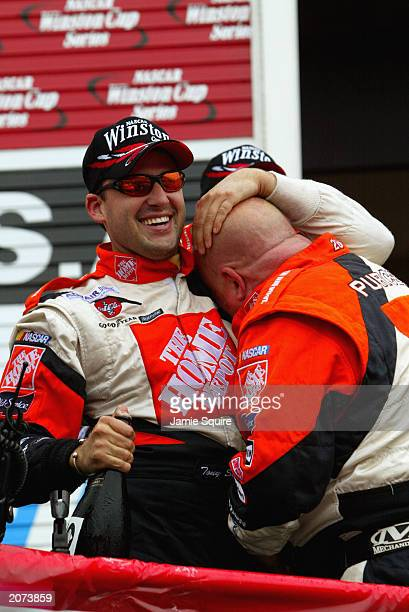 Tony Stewart driver of the Joe Gibbs Racing Chevrolet Monte Carlo celebrates with crew members in Victory Lane after winning the NASCAR Pocono 500 at...