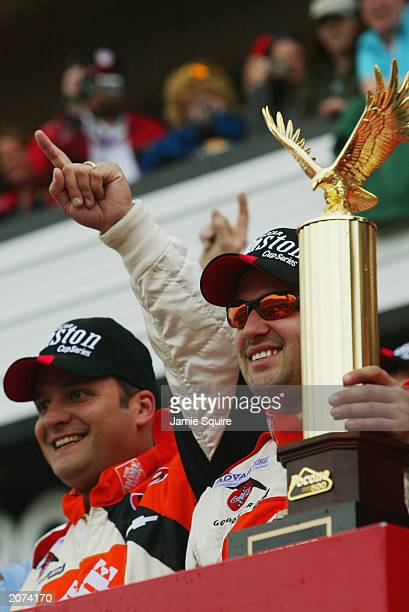 Tony Stewart driver of the Joe Gibbs Racing Chevrolet Monte Carlo celebrates with crew chief Greg Zippadelli in Victory Lane after winning the NASCAR...