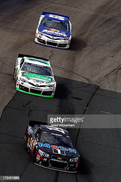Tony Stewart driver of the Mobil 1 Chevrolet leads Kyle Busch driver of the Interstate Batteries Toyota and Brian Vickers driver of the Aaron's Dream...