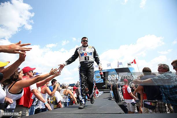 Tony Stewart driver of the Mobil 1/Bass Pro Shops Chevrolet greets fans during the NASCAR Sprint Cup Series Pure Michigan 400 at Michigan...