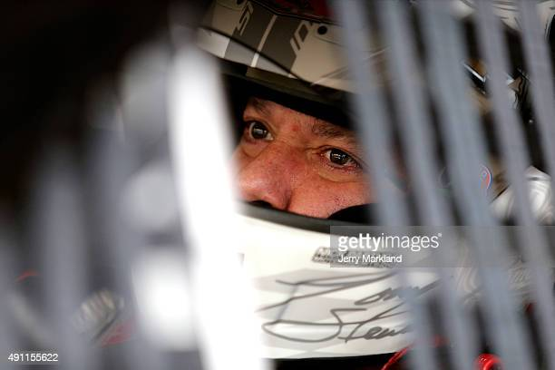 Tony Stewart driver of the Mobil 1/Bass Pro Shops Chevrolet sits in his car in the garage area during practice for the NASCAR Sprint Cup Series AAA...