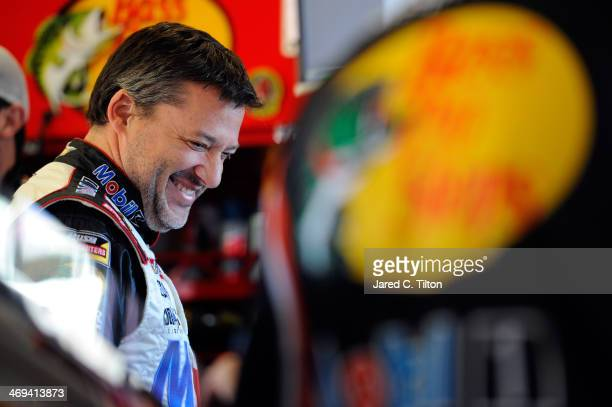 Tony Stewart driver of the Mobil 1/Bass Pro Shops Chevrolet stands in the garage during practice for the NASCAR Sprint Cup Series Sprint Unlimited at...