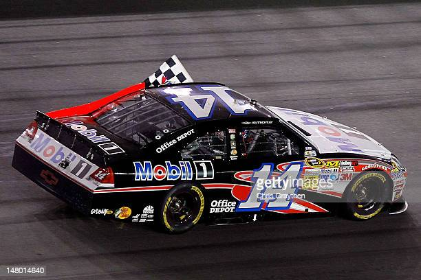 Tony Stewart driver of the Mobil 1/Office Depot Chevrolet celebrates on track after winning the NASCAR Sprint Cup Series Coke Zero 400 Powered by...