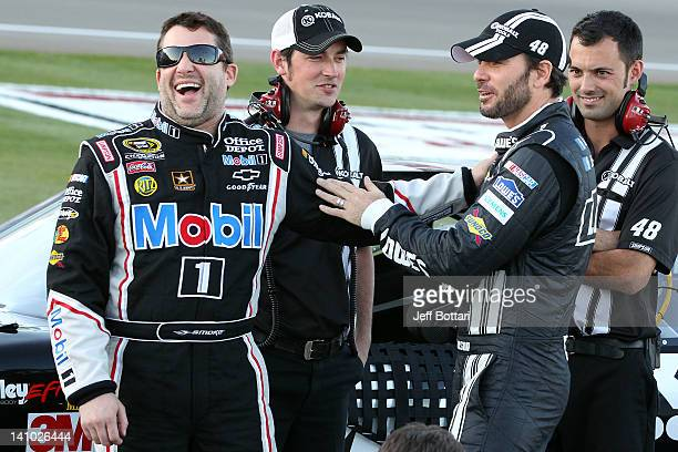 Tony Stewart driver of the Mobil 1/Office Depot Chevrolet talks with Jimmie Johnson driver of the Lowe's/Kobalt Tools Chevrolet during qualifying for...