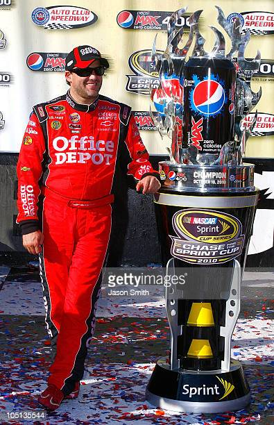 Tony Stewart driver of the Office Depot Chevrolet celebrates in victory lane after winning the NASCAR Sprint Cup Series Pepsi Max 400 on October 10...