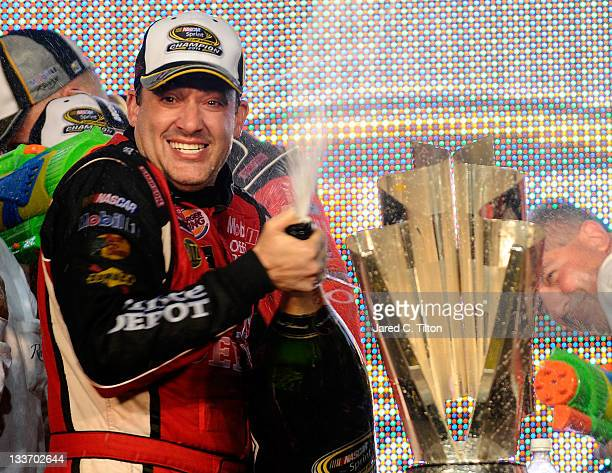 Tony Stewart driver of the Office Depot/Mobil 1 Chevrolet celebrates with the trophy in Victory Lane after winning the NASCAR Sprint Cup Series Ford...