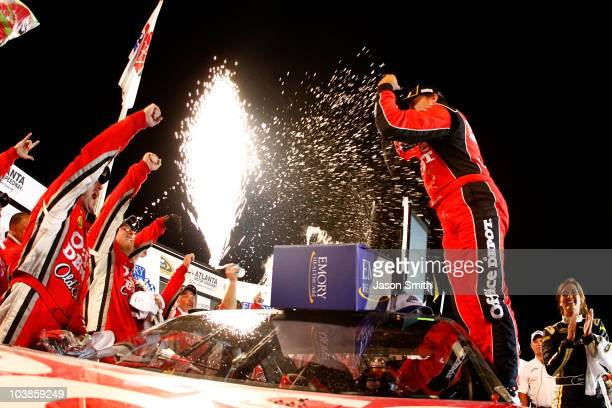 Tony Stewart driver of the Office Depot/Old Spice Chevrolet celebrates in Victory Lane after winning the NASCAR Sprint Cup Series Emory Healthcare...