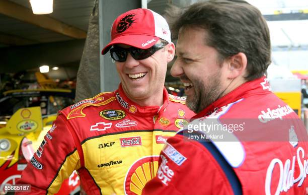 Tony Stewart driver of the Old Spice/Office Depot Chevrolet greets Kevin Harvick driver of the Shell/Pennzoil Chevrolet during practice for the...