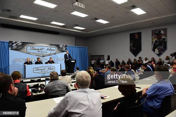 Tony Stewart driver of the StewartHaas Racing Chevrolet and coowner of StewartHaas Racing speaks with the media as Gene Haas coowner of StewartHaas...