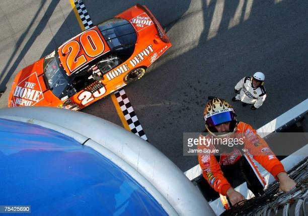 Tony Stewart driver of the The Home Depot Chevrolet climbs the fence to the starters' stand in celebration of winning the NASCAR Nextel Cup Series...