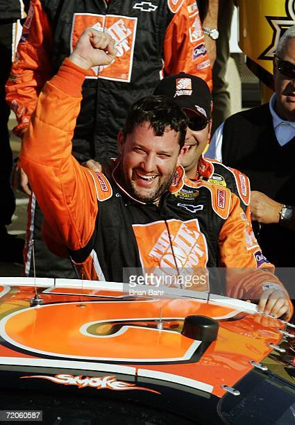 Tony Stewart, driver of the The Home Depot Chevrolet, reacts as he gets out of his car in victory lane after winning the NASCAR Nextel Cup Series...