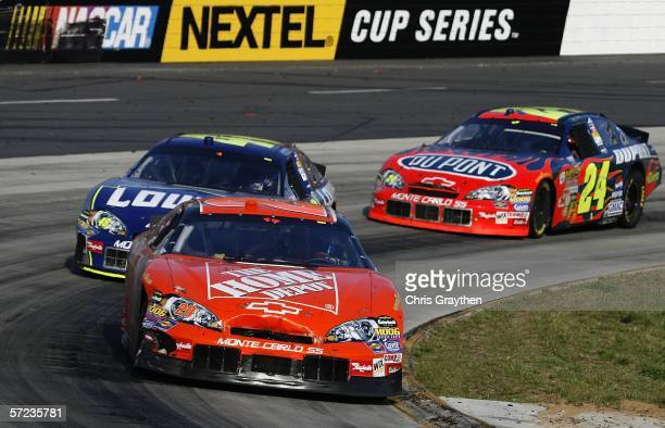 Tony Stewart drives the Home Depot Chevrolet ahead Jimmie Johnson driver of the Lowe's Chevrolet and Jeff Gordon driver of the DuPont Chevrolet...