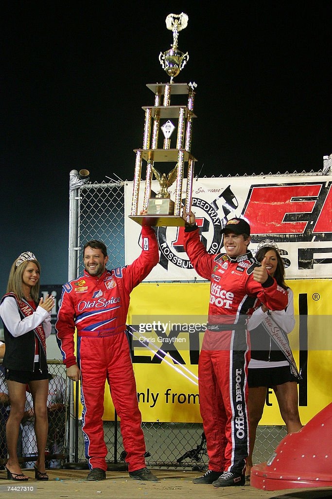 Tony Stewart (L) hands Carl Edwards the trophy for winning the Nextel Prelude to the Dream on June 6, 2007 at Eldora Speedway in New Weston, Ohio.