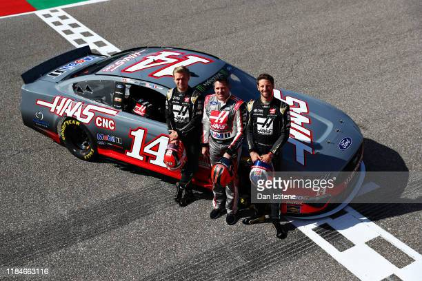 Tony Stewart , Kevin Magnussen of Denmark and Haas F1 and Romain Grosjean of France and Haas F1 pose for a photo before driving the No. 14 Haas...