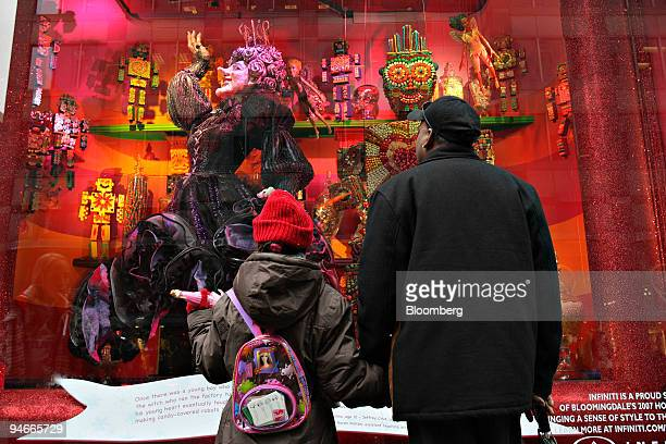 Tony Sumai right looks over a Bloomingdale's holiday window with Fhalini Ramkalawan outside Bloomingdale's in New York US on Tuesday Nov 20 2007 The...
