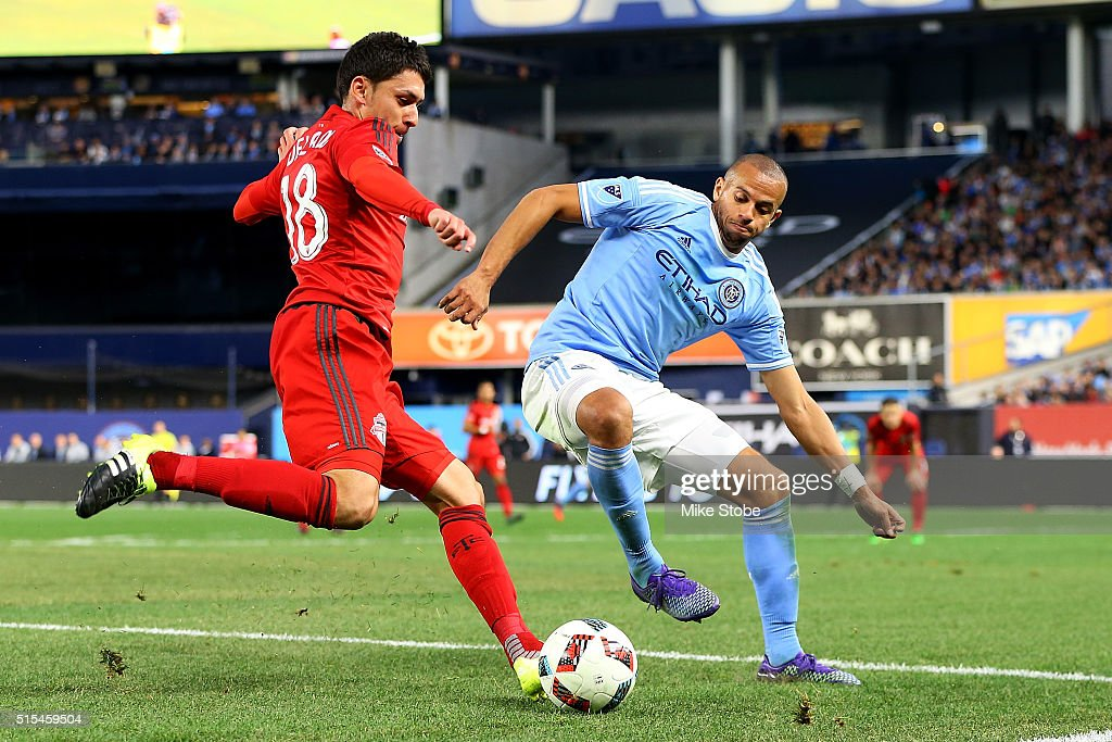 Tony Taylor #99 of New York City FC defends against Marco Delgado #18 of Toronto FC at Yankee Stadium on March 13, 2016 in the Bronx borough of New York City.