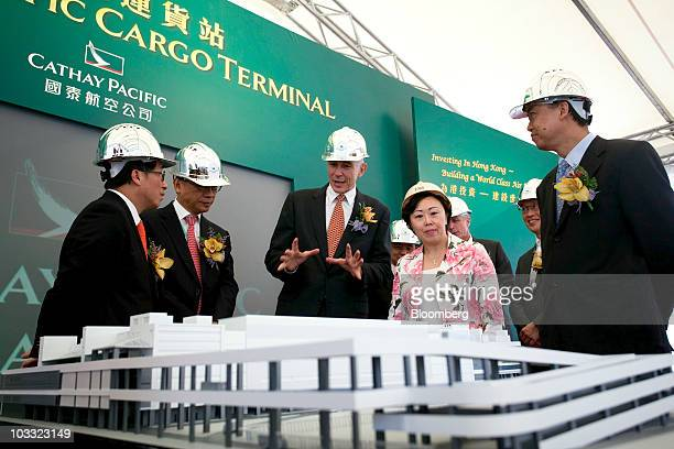 Tony Tyler chief executive officer of Cathay Pacific Airways Ltd center shows a model of the company's new cargo terminal to Eva Cheng Hong Kong's...