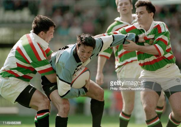 Tony Underwood of Newcastle Falcons playing for the World XV is tackled by his brother Rory Underwood and Stuart Potter of Leicester Tigers during...