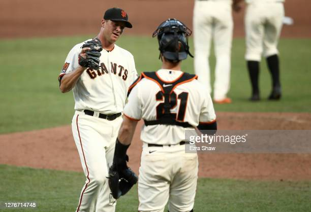 Tony Watson is congratulated by Joey Bart of the San Francisco Giants after they beat the San Diego Padres in game one of their double header at...