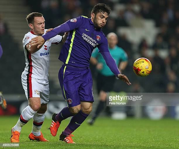 Tony Watt of Charlton Athletic attempts to move forward with the ball under pressure from Lee Hodson of Milton Keynes Dons during the Sky Bet...