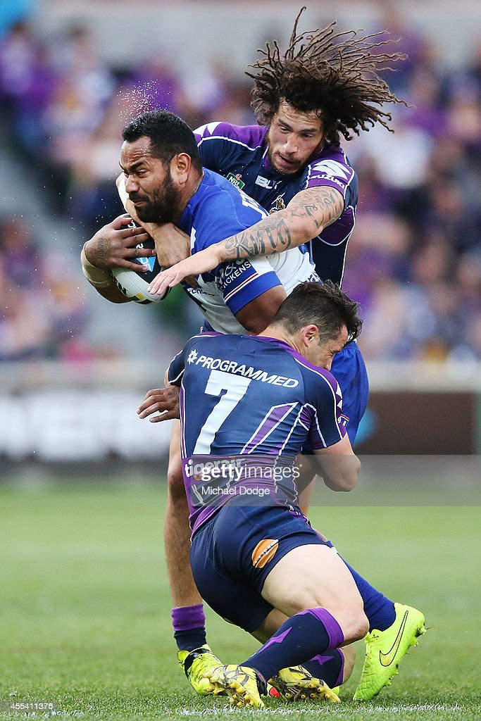 Tony Williams of the Bulldogs is tackled by Cooper Cronk and Kevin Proctor of the Storm (top) during the NRL 2nd Elimination Final match between the Melbourne Storm and the Canterbury Bankstown Bulldogs at AAMI Park on September 14, 2014 in Melbourne, Australia.