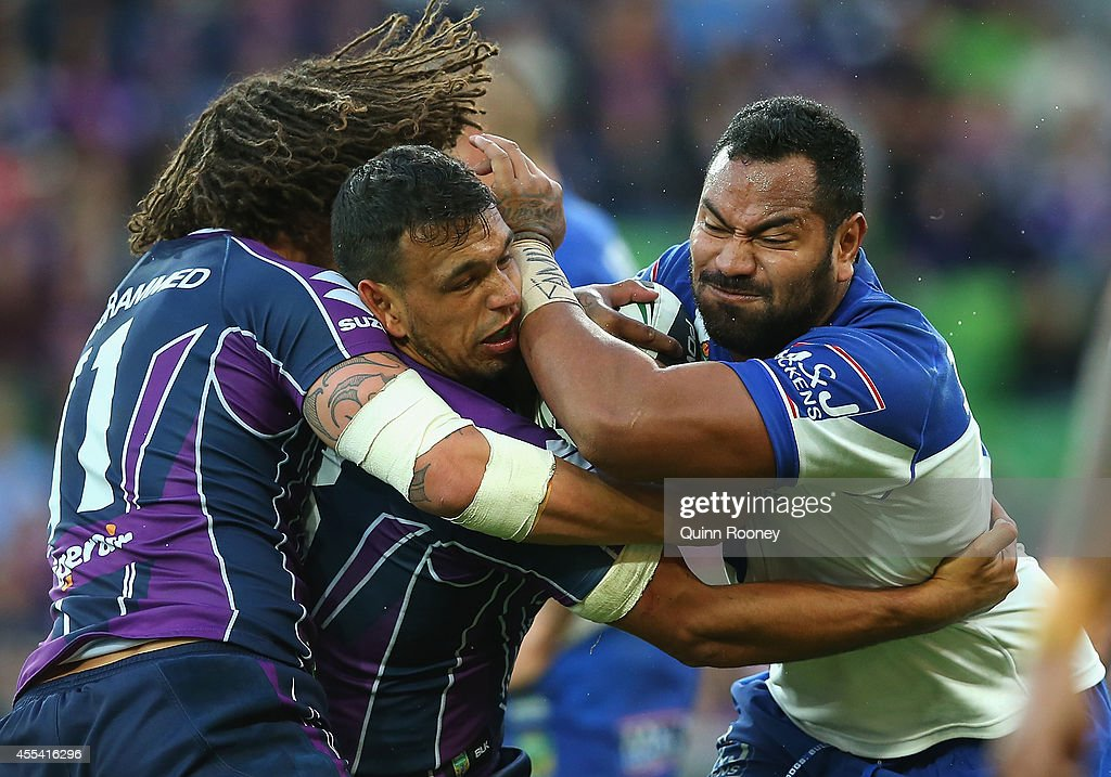 Tony Williams of the Bulldogs is tackled by Kevin Proctor and Will Chambers of the Storm during the NRL 2nd Elimination Final match between the Melbourne Storm and the Canterbury Bankstown Bulldogs at AAMI Park on September 14, 2014 in Melbourne, Australia.