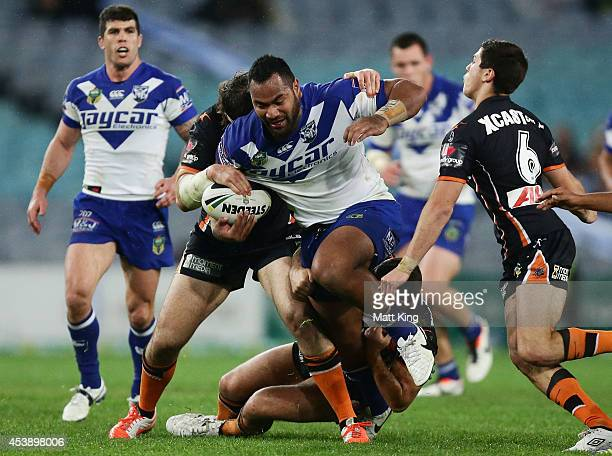 Tony Williams of the Bulldogs is tackled during the round 24 NRL match between the Canterbury Bulldogs and the Wests Tigers at ANZ Stadium on August...