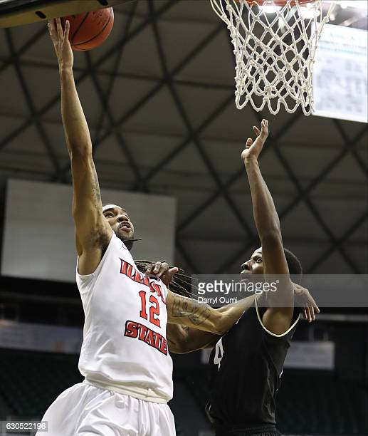 Tony Wills of the Illinois State Redbirds fends off Sterling Taplin of the Tulsa Golden Hurricane as he lays the ball in during the first half of the...