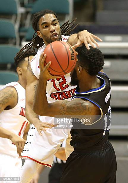 Tony Wills of the Illinois State Redbirds swats at the ball as he guards Jaleel Wheeler of the Tulsa Golden Hurricane during the first half of the...