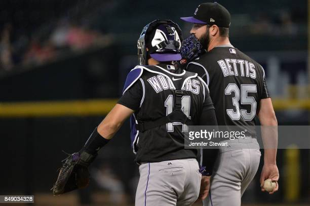 Tony Wolters and Chad Bettis of the Colorado Rockies talk on the field in the MLB game against the Arizona Diamondbacks at Chase Field on September...