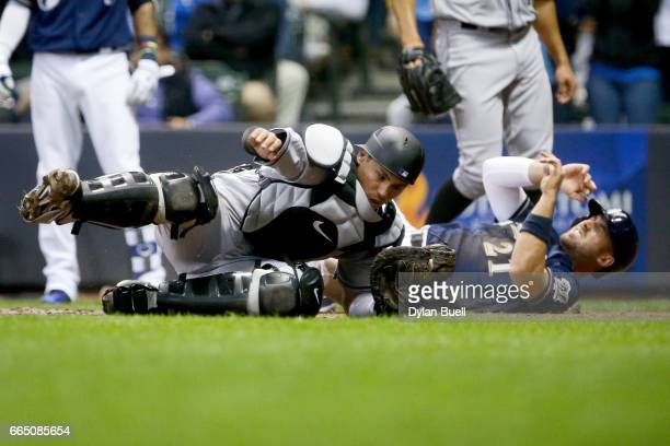 Tony Wolters of the Colorado Rockies and Travis Shaw of the Milwaukee Brewers collide at home plate in the fourth inning at Miller Park on April 4...