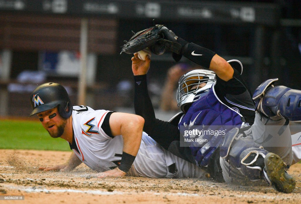 Tony Wolters #14 of the Colorado Rockies attempts to retag Bryan Holaday #28 of the Miami Marlins after he slid into home plate for the score in the eighth inning against the Colorado Rockies at Marlins Park on April 29, 2018 in Miami, Florida.