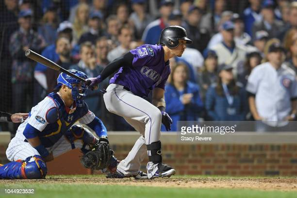 Tony Wolters of the Colorado Rockies hits a RBI single to score Trevor Story in the thirteenth inning against the Chicago Cubs during the National...