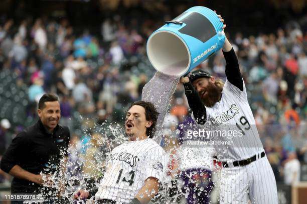 Tony Wolters of the Colorado Rockies is doused with water by Charlie Blackmon during his post game interview after hitting a game winning sacrifice...