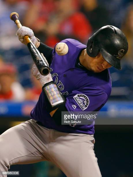 Tony Wolters of the Colorado Rockies is hit in the chest by a pitch while attempting to sacrifice in the eighth inning of a game against the...