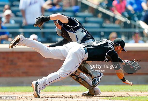 Tony Wolters of the Colorado Rockies makes a catch on a pop up in the fourth inning against the New York Mets as he collides with teammate Daniel...