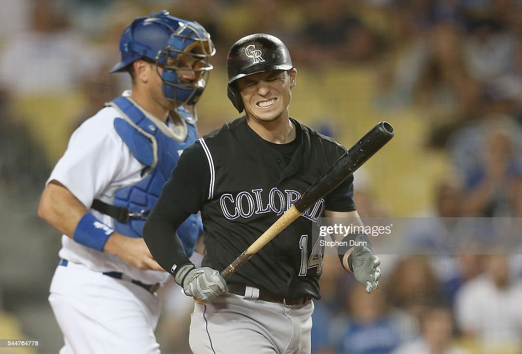 Tony Wolters #14 of the Colorado Rockies reacts aftre strking out swinging with a runner on second for the second out of the fifth inning against in front of catcher A.J. Ellis #17 of the Los Angeles Dodgers at Dodger Stadium on July 2, 2016 in Los Angeles, California.