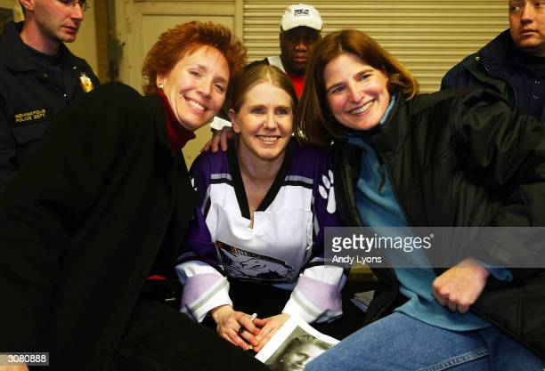 Tonya Harding poses for a picture with two fans after a boxing exhibition during the second period intermission at the Colorado Eagles versus...
