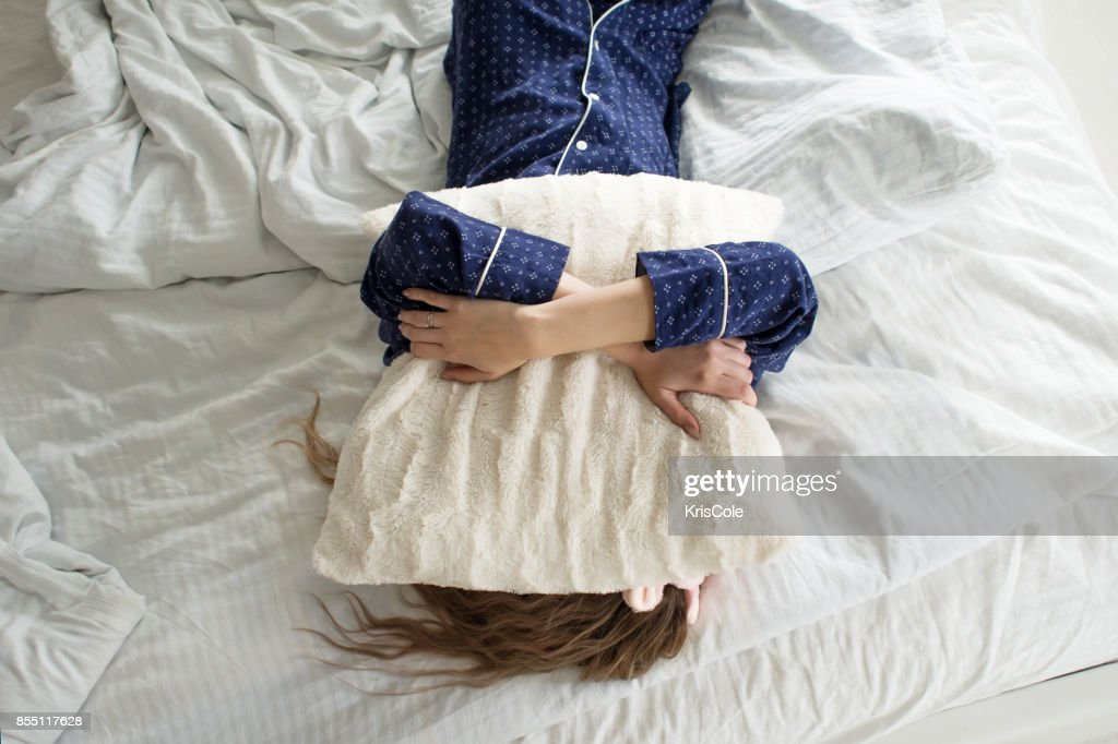 Too lazy to get out of bed, a woman covers her face with a pillow : Stock Photo