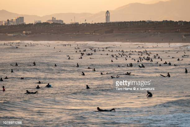 Too many surfers on Kugenuma Beach in Fujisawa city in Japan in the sunset