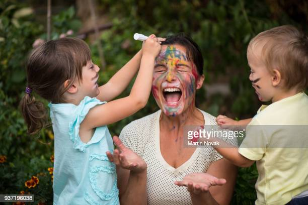 too much creativity - children painting mother's face - spaß stock-fotos und bilder