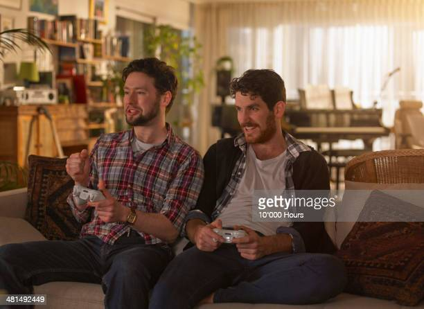 too young men playing video games - leisure games ストックフォトと画像