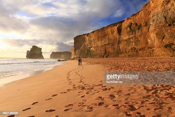Took in Great Ocean Road, a couple are taking photo in the beach near sunset time.