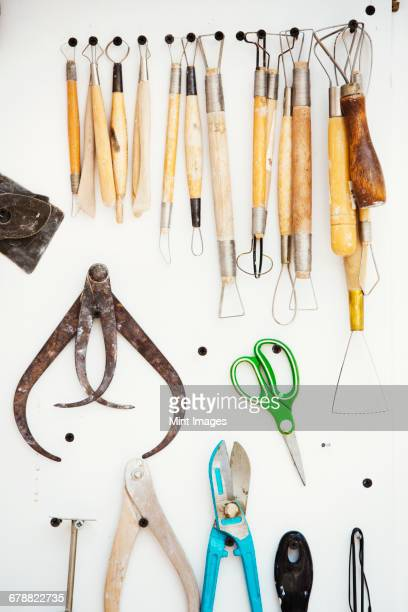 A tool board, with brushes, hand tools and pliers and curved shaping tools, callipers hanging on the wall.