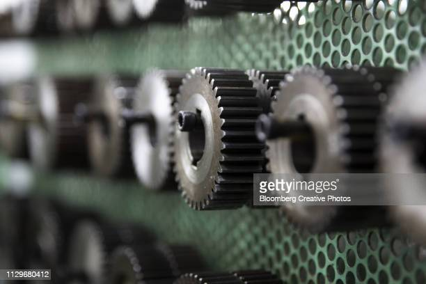tools for manufacturing gears are seen on the production line of a factory - maschinenteil hergestellter gegenstand stock-fotos und bilder